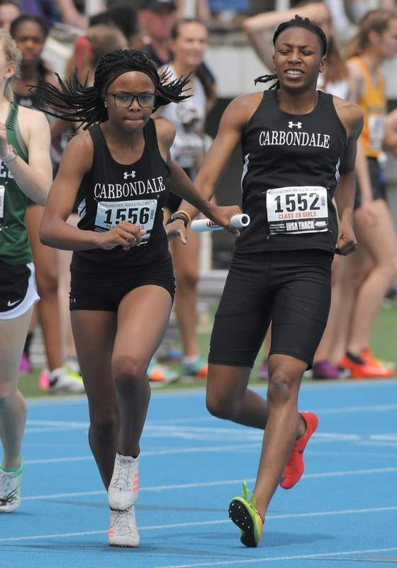 Joe Lewnard/jlewnard@dailyherald.comCarbondale's Serenity Riley, left, takes the baton farom Akira Custer in the 1,600-meter relay during the Class 2A girls state track and field preliminaries in Charleston Friday.