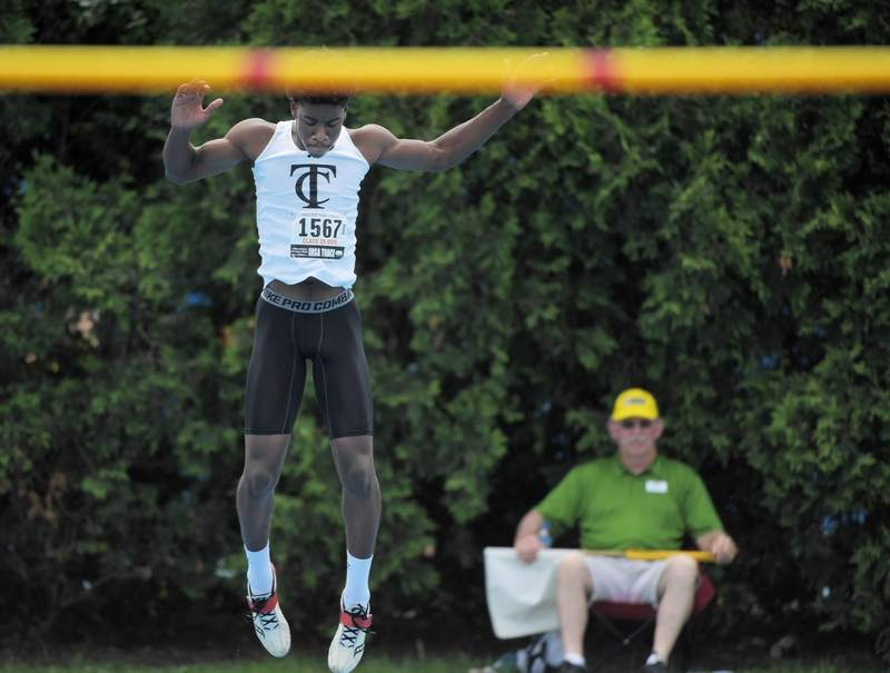 Carbondale's Martiez Pinnick warms up before an attempt in the high jump at the IHSA boys state track finals in Charleston Saturday.
