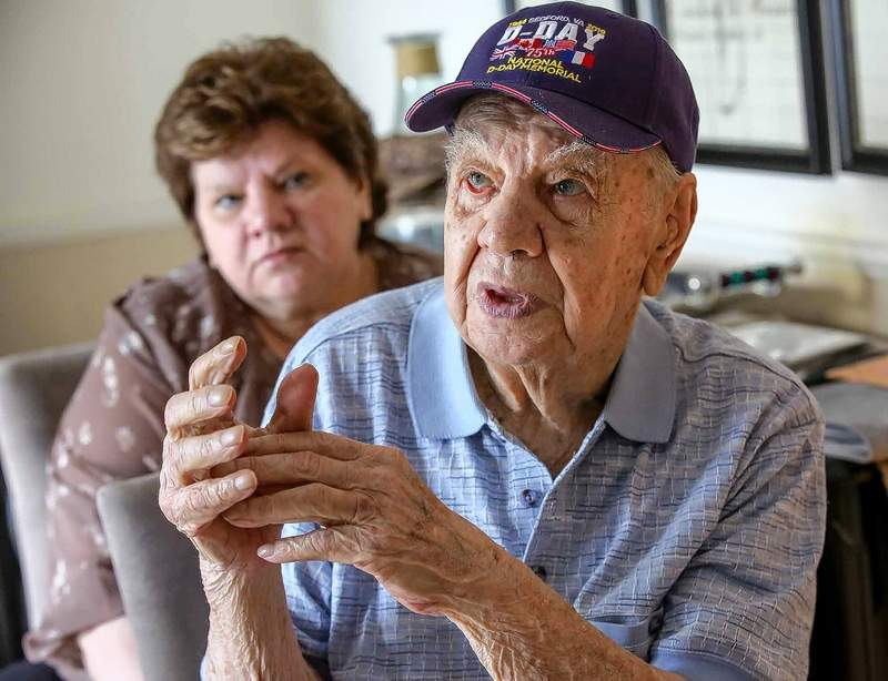 "Carole Trojan listens to her father, Walter Trojan of Bloomingdale, tell a story from his experience on D-Day. ""Those were desperate days,"" he said of the Battle of Omaha. ""We just had a toehold."""