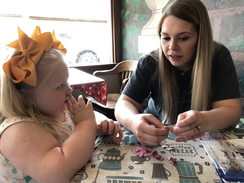 Kelsey Williamson, right, talks to her daughter, Salem, over brunch at The Buzz in Benton last week.  Kelsey's order from an online store added a twist to the family's life.
