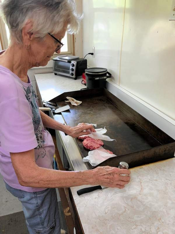 """Sue Jansco starts preparing a couple of """"Sadie Burgers,"""" made popular by her late mother-in-law."""
