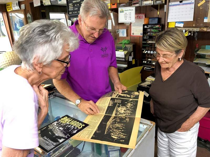 From left, Sue Jansco, Dave McNeal, and JoAnn McNeal, look through memorabilia detailing the legendary pool tournaments at the Showbar, also owned by the Jansco family.