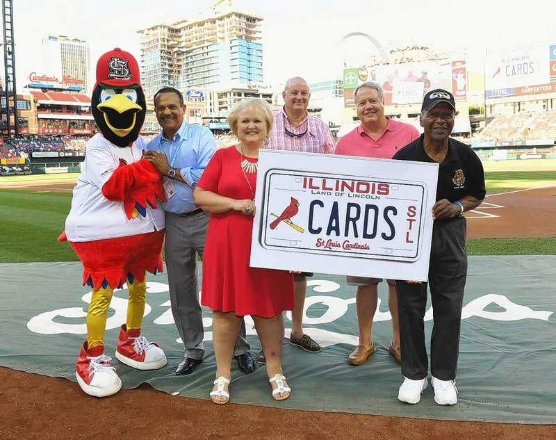 Illinois Secretary of State Jesse White (far right) is shown here with Vicki Bryant (red dress), vice president of Event Services and Merchandising for the St. Louis Cardinals, Fredbird and others, after it was announced recently at Busch Stadium that Cardinals license plates would soon be available to Illinois residents with sales benefiting public schools.