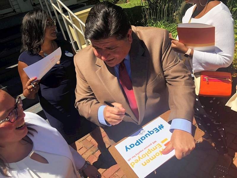 Gov. J.B. Pritzker puts his signature on a sign for a supporter of House Bill 834 during a ceremony Wednesday in Chicago. Pritzker signed into law HB 834, which prohibits employers in Illinois from asking job applicants about their salary history. Advocates say the measure will help stem wage inequality among men and women.