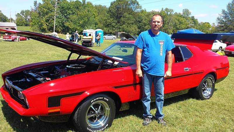 Jamie Prince of Mayfield, Kentucky stands next to his 1971 Ford Mach 1 Mustang.