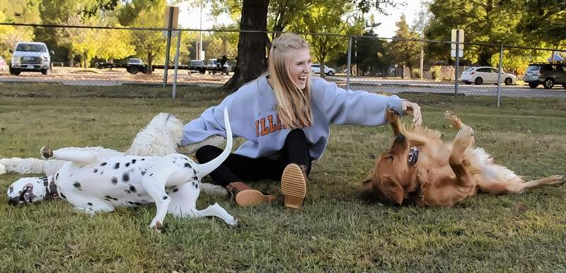 Callie Barrett enjoys a laugh as she is surrounded by some canine friends.