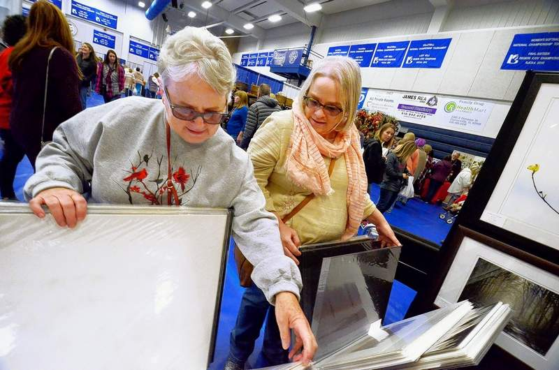 Jane Terry, left, and her daughter Anne, both of Carbondale, browsed through a bin full of nature photographs by Goreville photographer David Hammond over the weekend at the John A. Logan College Gym, site of the 44th Annual AutumnFest.