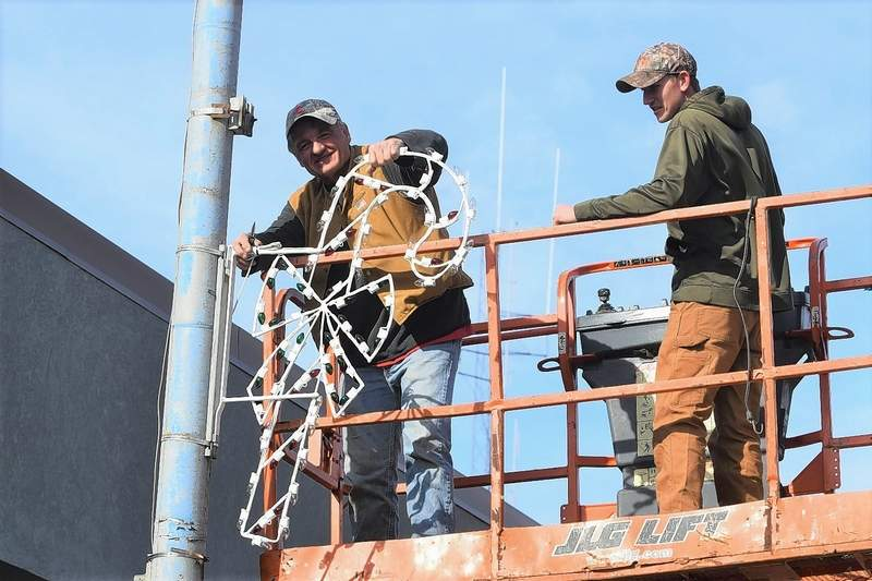City of Harrisburg workers Joe Gholson, left, and Dakota McGowan put up a candy cane decoration in front of Point Blank Range in Harrisburg Wednesday afternoon. City workers used the unseasonably warm weather to put up decorations for the holidays.