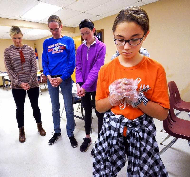 Anna McCarty, 11, right, paused for a prayer blessing upon the food with others in her youth group and parent volunteers who gave up their own holiday to prepare and serve a traditional Thanksgiving feast at the Marion Ministerial Alliance office on Calvert Street in Marion Thursday.