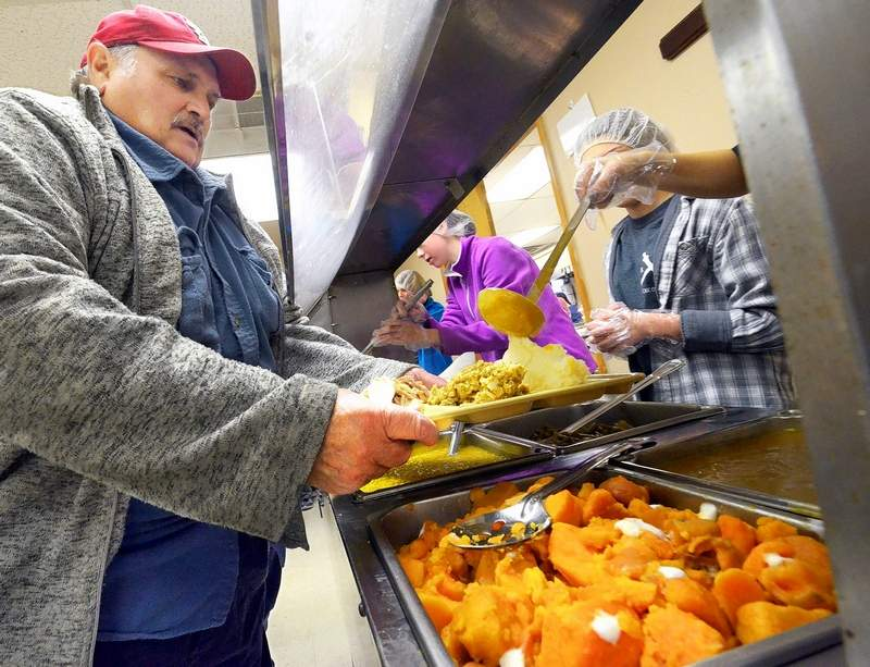 """Marion resident Michael Pike was among the guests Thanksgiving Day at the Marion Ministerial Alliance office site of the 19th annual free holiday feast which was prepared and served by local Catholic youth and their parent volunteers. Pike called the meal """"geat,"""" adding, """"I always try to come every year."""""""