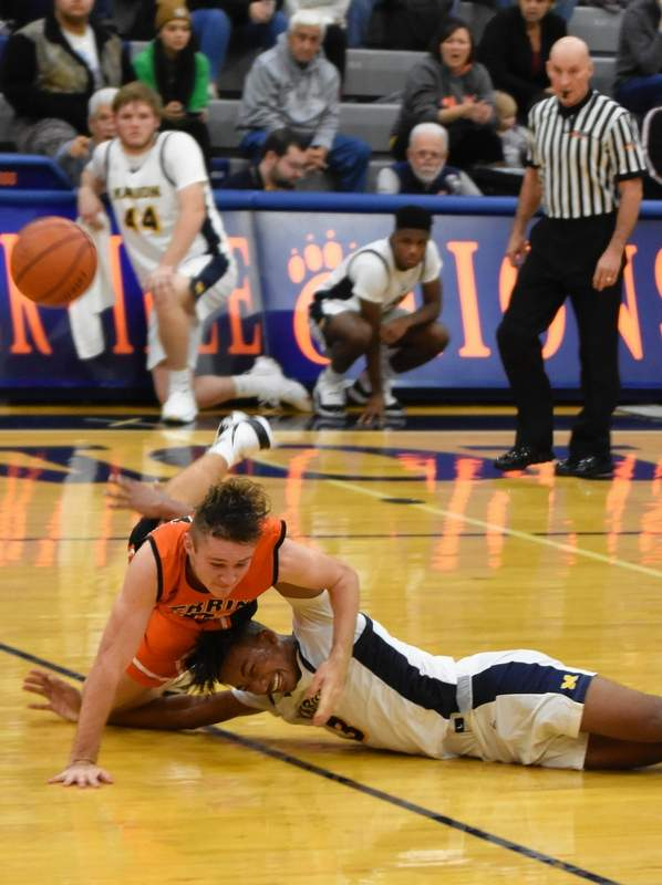 Herrin's Jake Baumgarten and Marion's Venson Newsom fight over a loose ball at midcourt during opening action in the Pyramid Plus Tournament at Carterville last week.