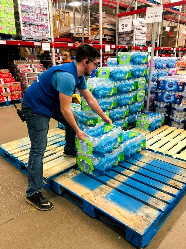 Jonah Davis of Herrin keeps packaged water stocked during the COVID-19 crisis at Sams Club in Marion.