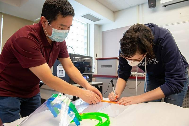 Lingguo Bu, associate professor of curriculum and instruction, left, and Alex Apgar, a senior in geology who works at the SIU STEM Education Research Center, work on assembling face shields after making the parts on a 3D printer at SIU. Faculty are using 3D printing technology to manufacture the shields used to keep workers safe during the COVID-19 health emergency.