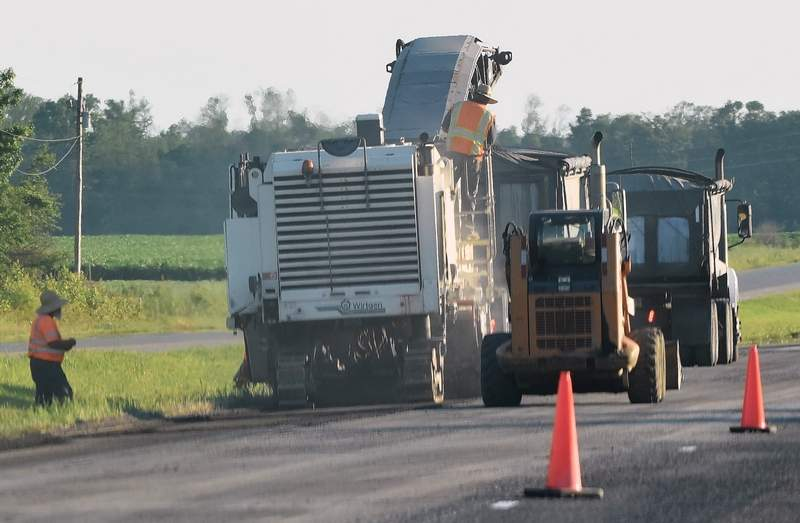 Road construction workers operate equipment Thursday evening along U.S. Route 45 between Eldorado and Muddy.