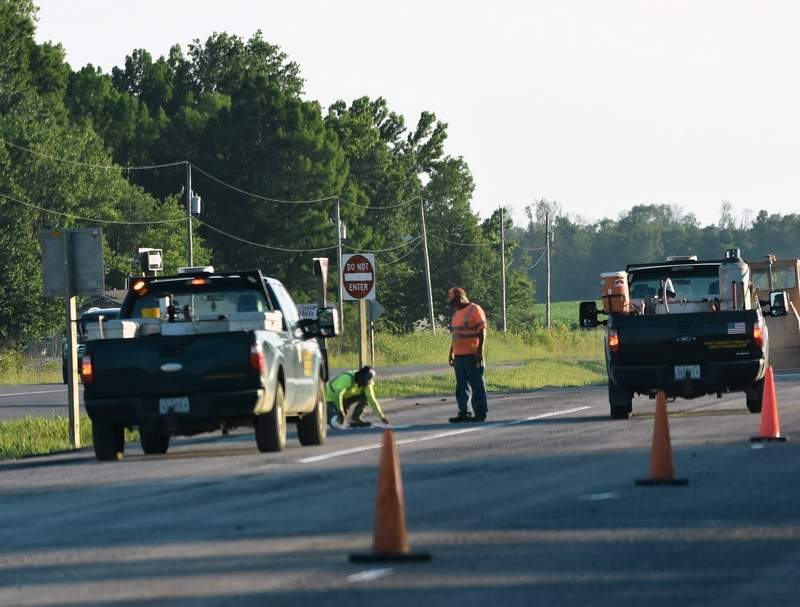 Two road construction workers mark the pavement on the left shoulder of US 45 Thursday evening.