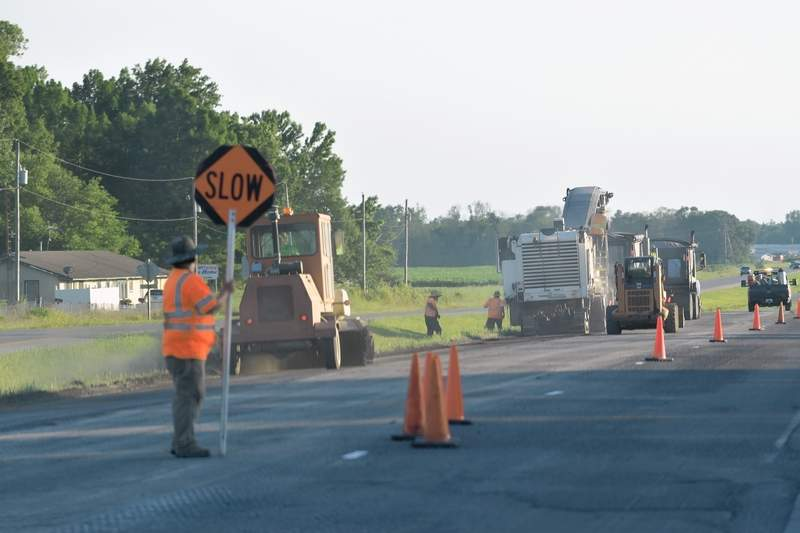 A flagger holds a sign during road construction Thursday evening along US 45 between Eldorado and Muddy.