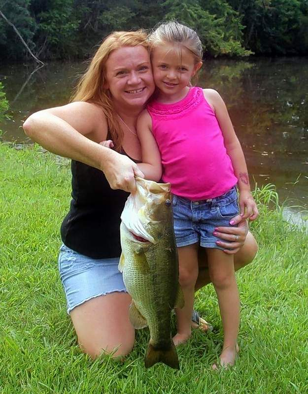 Sophie Walker, right, needed the help of her mom, Kathleen, to drag this big fish from a local farm pond.