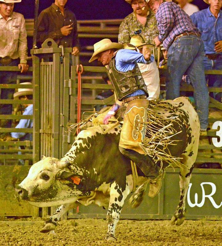 John Stout, of Galatia, competes in the bull riding Friday evening.....