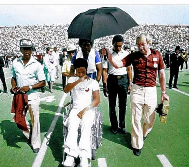 Mark Hemphill gets choked up listening to the student section cheer his name, at halftime of the 1980 game at which he was honored. Fred Huff holds the umbrella to shield Hemphill from the sun, and Gale Sayers stands behind. Hemphill was wheeled in by his brother.