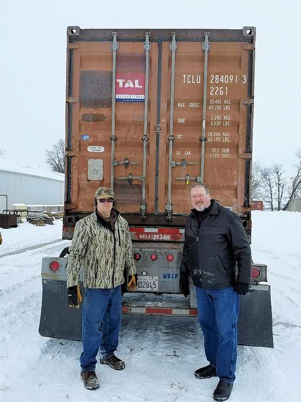 Fager-McGee Resilient Building Division team members Gerald DeNeal, left, and Eric Gregg stand next to a shipping container loaded and bound for Australia Wednesday afternoon.