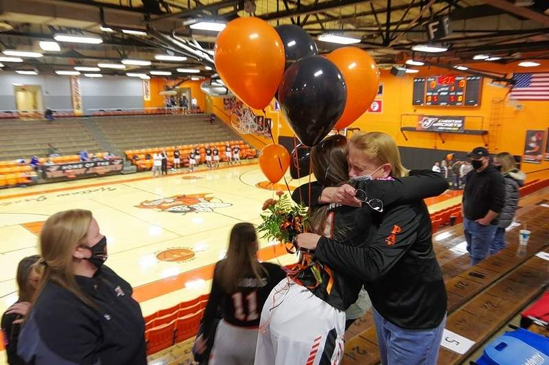 CHS Lady Jacket basketball player Peyton Clendenin hugs Janelle Knowles during a memorial tribute to for Pat Knowles, former Lady Jacket head coach, who died unexpectedly last March. The ceremony was held prior to the start of the Lady Jacket Senior Night game on feb. 25, when the Lady Jackets presented Mrs. Knowles with flowers and orange and black balloons in memory of her husband.