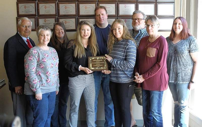 Du Quoin Chamber of Commerce Board Member Jessica Holder presents the Business of the Year plaque to the Weekly-Press staff. From left, Jerry Reppert, Amanda Morgenstern, Stephanie Waller, Jessica Holder, Pete Spitler, Emily Shanklin, Jeff Egbert, Pat Bathon and Amanda Holmes.