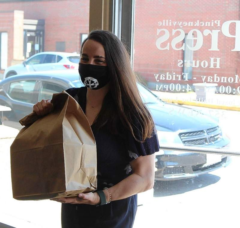 Abby Ancell brings in food from St. Nicholas Brewing Company for the celebration at the Pinckneyville Press/Du Quoin Weekly office.