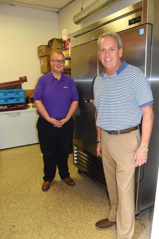 TRAVIS DENEAL PHOTOAetna Better Health of Illinois representative Jeffrey Isbell, left, and state Sen. Dale Fowler stand in front of the new freezer unit at Heaven's Kitchen in Harrisburg.