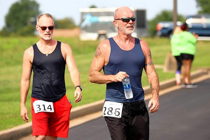 Tim Kee, right, with his husband Rick Wade, after a Heartland Regional Medical Center 5K Run in August 2019.