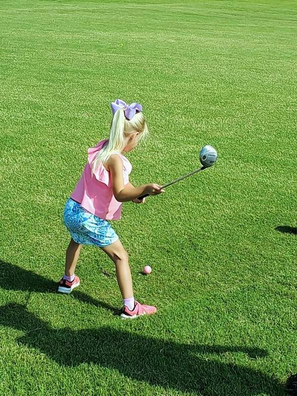 A junior golfer prepares to strike a golf ball at the SI Clothes For Kids Junior Golf Tournament Thursday.