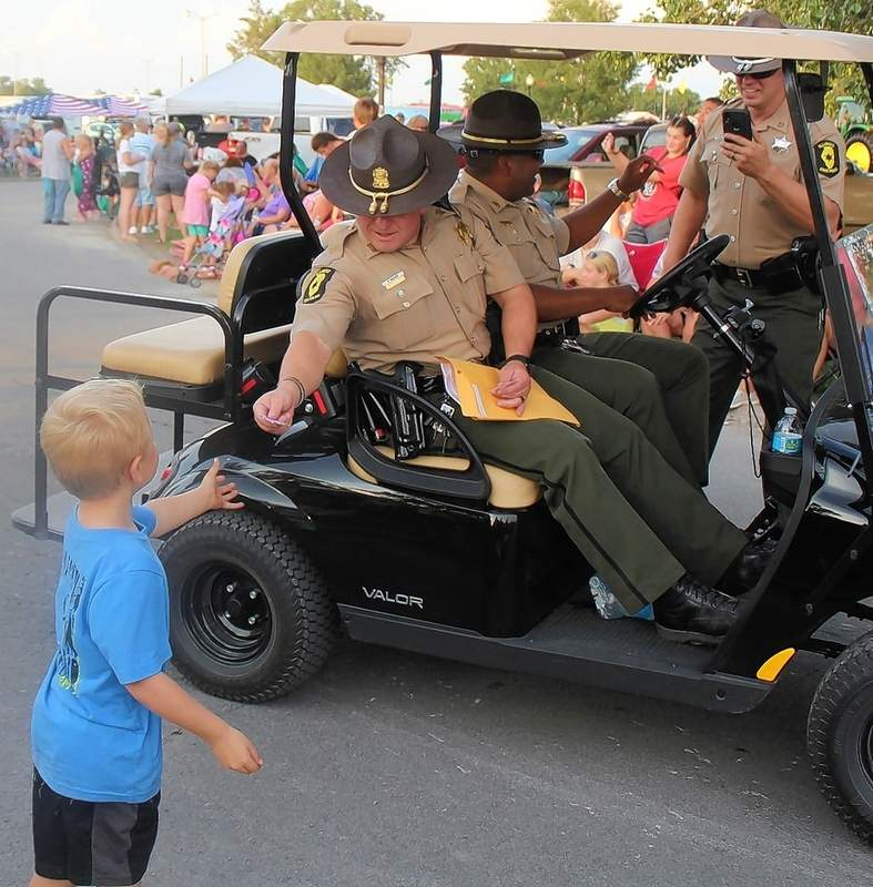 Members of the Illinois State Police headquartered in Du Quoin walk and ride the parade, and take time to greet a small fan.